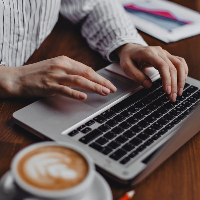 Female hands press laptop keys while sitting at wooden table with white cappuccino cup